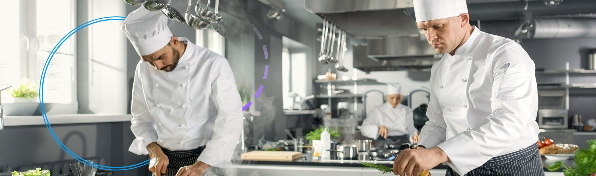 Three cooks working in restaurant kitchen